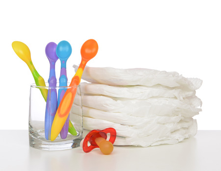 incontinence: New born child stack of diapers, nipple soother baby feeding spoons on a white background