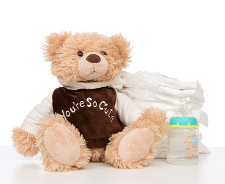 incontinence: Child stack of diapers and baby feeding bottle with water and soft teddy bear toy on a white background