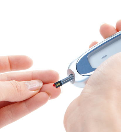 blood glucose: Dependent first type Diabetic patient measuring glucose level blood test using ultra mini glucometer and small drop of blood from finger and test strips isolated on a white background