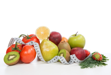 Diet weight loss breakfast concept with tape measure organic green apple,  tomatoes, strawberries, parsley, kiwi, grapefruit, pear  on a white background photo