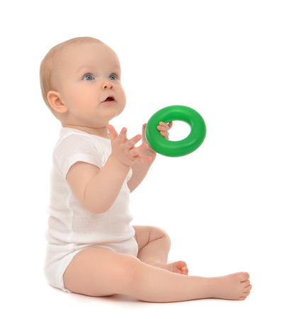 Infant child baby boy toddler playing holding green circle in hand on a floor on and looking up isolated a white background