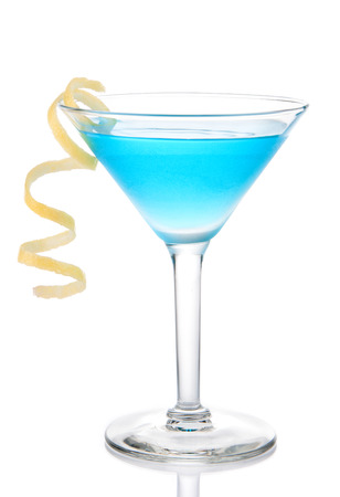 Blue tropical martini cocktail with yellow lemon spiral isolated on a white background