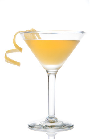 Yellow banana cocktail in martini glass with lemon twist isolated on a white background