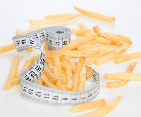 French fries chips meal with tape measure on white background. Healthy weight loss diet concept. photo