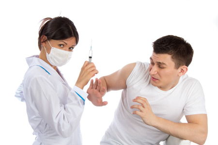 Doctor or nurse with syringe needle and man scary of injection vaccination phobia concept against white background. photo