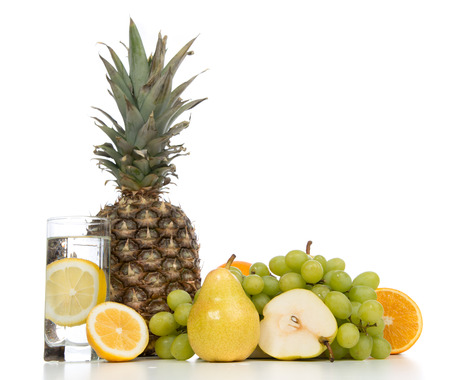 Weight loss breakfast concept with fruits organic pear, orange, lemon juice, pineapple, grapes and glass of water with lemon on a white background photo