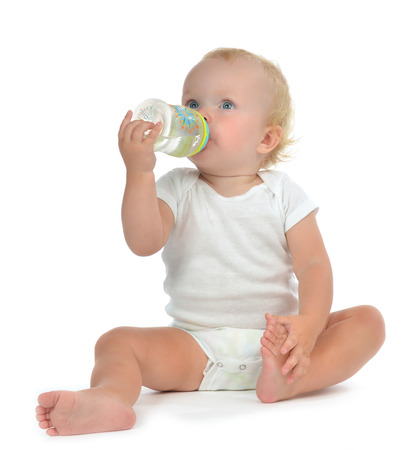 Infant child baby toddler sitting and drinking water from the feeding bottle on a white background Archivio Fotografico