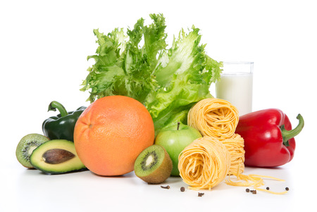 Diet weight loss breakfast concept. Fruits and vegetables organic green and red pepper, tomatoes, almonds, fresh salad, spaghetti, grapefruit, glass of milk on a white background photo