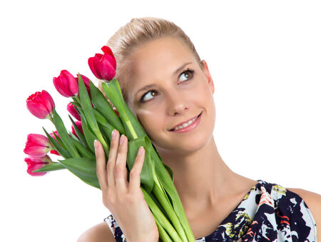 Young pretty woman holding a bunch of red tulips bouquet of flowers smiling on white background photo