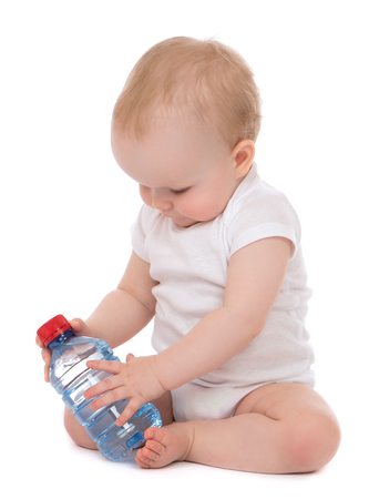 Infant child baby sitting with bottle of drinking water in diaper isolated on white  Reklamní fotografie