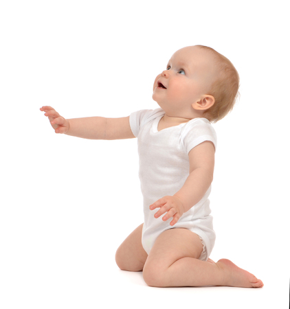 Infant baby toddler sitting hand pointing and looking up isolated on a white  photo