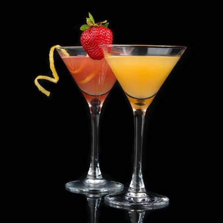 Two cocktails red cosmopolitan cocktail decorated with citrus lemon twist and yellow martini drink with strawberry isolated on a black  photo