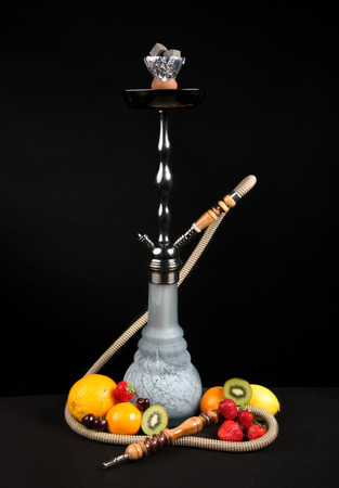 Beautiful traditional shisha hookah or Sheesha water pipe with exotic fruits on a black