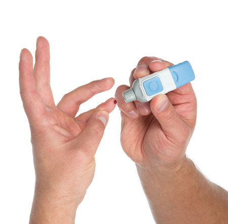 Diabetes lancet in hand prick finger to make punctures to obtain small blood specimens for blood glucose, hemoglobin level test using glucometer isolated on a white  Banque d'images