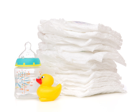 incontinence: New born child stack of diapers nipple soother baby feeding milk bottle with water and yellow duck on a white