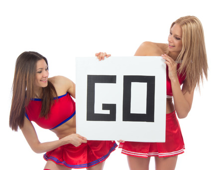 Cheerleader dancer girls from cheerleading team smiling hold sign in hand for text space  isolated on a white background photo