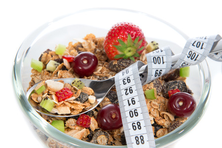 Diet weight loss concept tape measure spoon muesli cereals bowl almond, pine nuts, walnut, raisins, oat and wheat flakes, fresh fruits kiwi, strawberry pieces, banana, pomegranate seeds