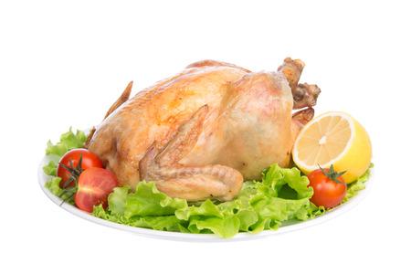 pollos asados: Adornado pollo thanksgiving asado en un plato decorado con tomates de la ensalada de limón aislado en un blanco
