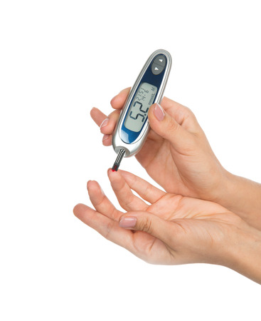 Diabetes patient measuring glucose level blood test with glucometer on a white  photo