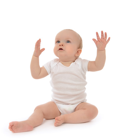 Infant child baby toddler sitting hands up isolated on a white background Stockfoto