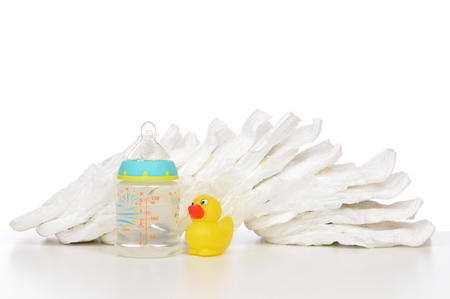 incontinence: New born child stack of diapers nipple soother baby feeding milk bottle with water and yellow duck on a white background Stock Photo