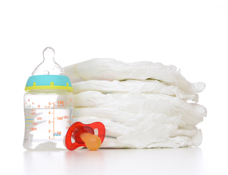 New born child stack of diapers nipple soother and baby feeding bottle with water on a white background Archivio Fotografico