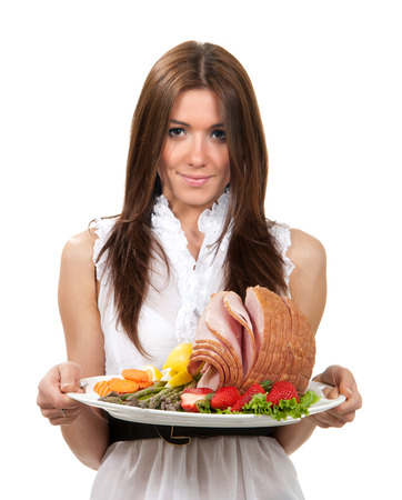 Woman hold plate with smoked sliced ham meat decorated with fruits and vegetables for dinner evening isolated on a white background Stock Photo