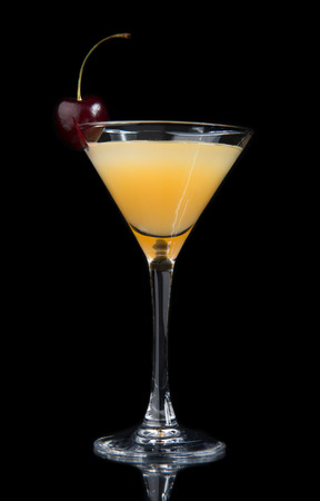 Yellow pineapple banana cocktail decorated with fresh cherry in martini cocktails glass isolated on a black background