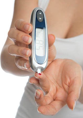 Diabetes patient measuring glucose level blood test using ultra mini glucometer and small drop of blood from finger and test strips isolated on a white background Archivio Fotografico