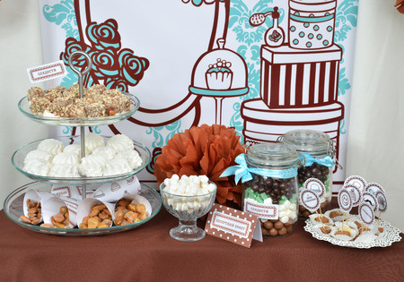 Homemade fancy set table with sweets candies, cake, marshmallows, zephyr, nuts, almonds, truffle as a present for birthday party photo