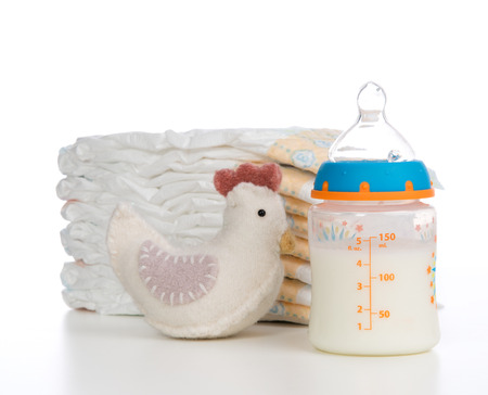 pampers: New born child composition stack of diapers toy and baby feeding bottle with milk on a white background