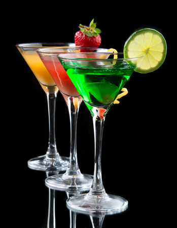 Three cocktails cosmopolitan cocktails decorated with citrus lemon twist yellow martini drink with strawberry isolated on a black background Foto de archivo