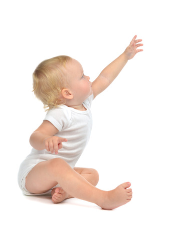 Infant child baby toddler sitting raise hand up pointing finger isolated on a white background