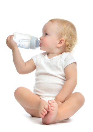 Infant child baby toddler sitting and drinking water from the feeding bottle on a white background Banco de Imagens