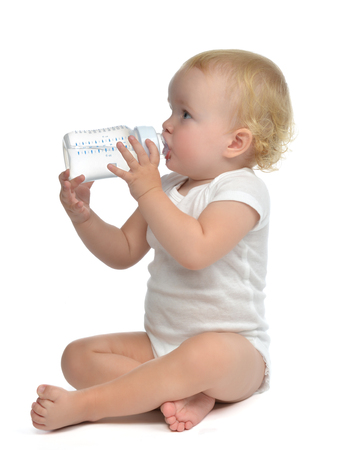 nipple breast: Infant child baby toddler sitting and drinking water from the feeding bottle on a white background Stock Photo