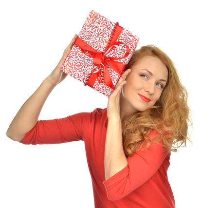 looking in corner: Christmas gift woman with wrapped christmas present smilling happy looking at the corner isolated on a white background