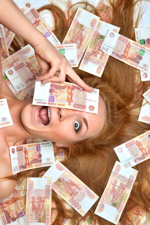 five dollars: Surprised young woman lying down with many cash money five thousand russian rubles notes in hand looking at the camera isolated on a white background