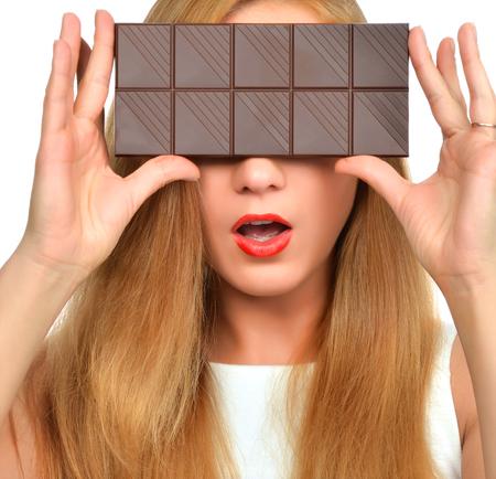 salud sexual: Hermosa chica ocultar sus ojos con barra de chocolate tiro del estudio aislado en el fondo blanco Foto de archivo