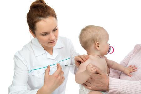 inyeccion intramuscular: Los médicos mano con jeringa vacunación infantil bebé tiro inyección de la gripe aislado en un fondo blanco Foto de archivo