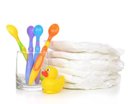 nappies: New born child stack of diapers baby little spoons in glass and yellow duck toy on a white background Stock Photo