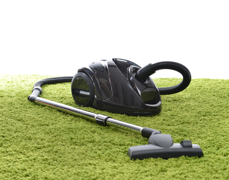 vacuum cleaner: Powerfull black Vacuum cleaner on green carpet floor on the white background