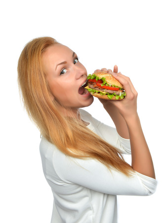 Fast food concept. Woman eating tasty unhealthy burger sandwich in hands hungry getting ready to eat isolated on a white background