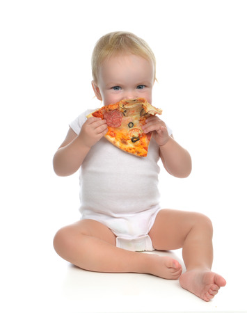 Infant child baby toddler sitting enjoy eating slice of pepperoni pizza with tomatoes cheese isolated on a white background Standard-Bild