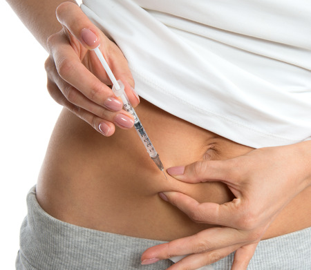 shot: Diabetes patient insulin shot by syringe with dose of lantus, subcutaneous abdomen vaccination isolated on a white background Stock Photo