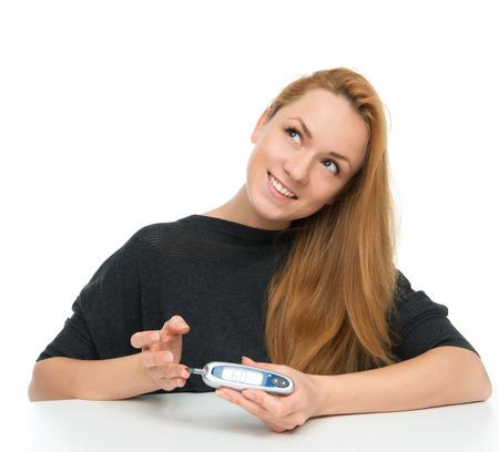 blood glucose level: Diabetes patient woman measuring glucose level blood test with glucometer on a white background Stock Photo