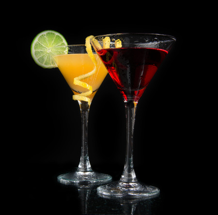 Two cocktails red cosmopolitan cocktail decorated with citrus lemon twist and yellow martini margarita drink with lime on a black background photo
