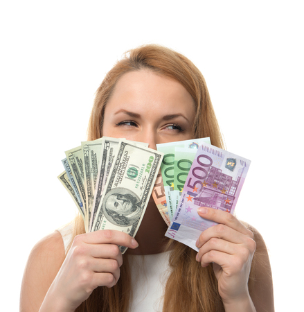Happy young woman holding up cash money five one fifty hundred euro in one hand and dollars in other compare thinking looking at the corner isolated on a white background photo