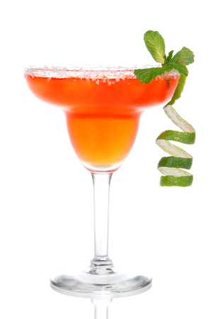 Red Margarita cocktail with mint and lime spiral in chilled salt rimmed glass with tequila orange syrup crushed ice in cocktails glass isolated on white background
