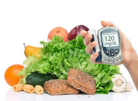 Diabetes concept. Meten van glucose niveau bloedtest op biologisch voedsel groenten en fruit achtergrond Stockfoto