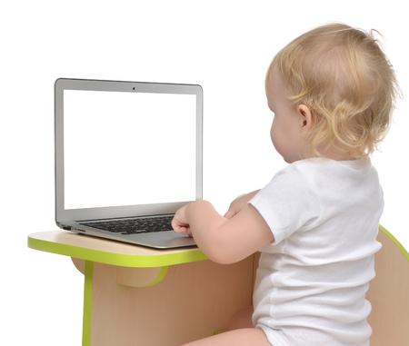 �infant: El ni�o del ni�o ni�a sentada con las manos que pulsan en el teclado del ordenador port�til moderno equipo inal�mbrico aislado en un fondo blanco Foto de archivo